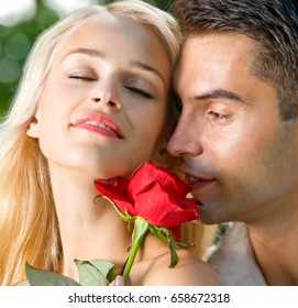 Young happy amorous cheerful couple with rose, outdoor. Love, relationships and dating concept.