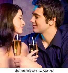 Young happy amorous couple with glasses of champagne on romantic date at restaurant or club