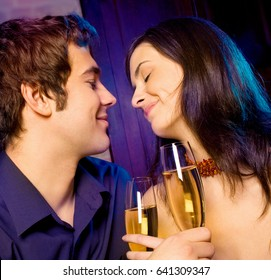 Young happy amorous couple with glasses of champagne on romantic date at restaurant or club. Love, party and date concept.
