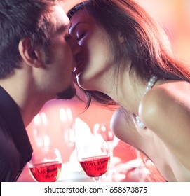 Young happy amorous couple kissing on romantic date, at restaurant. Love, relationships and dating concept.