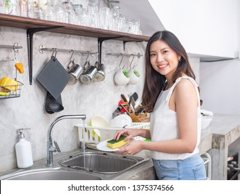 young  happy Asia woman is washing dishes while doing cleaning at home
