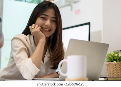 Young happy Asian businesswoman sitting in front of laptop computer and smiling.