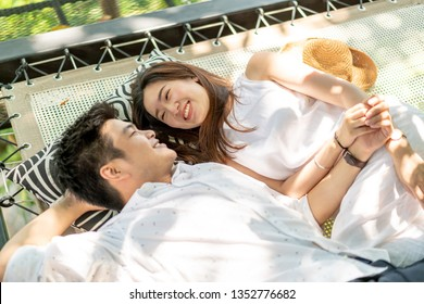 Young and happy Asian couple in love on cradle balcony