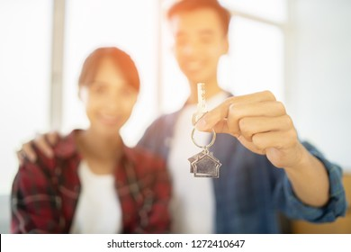 Young happy Asian couple smiling ,getting keys from new condominium real estate from agent. love buddy holding key ring to their new house or home hugging looking at camera,The joy of a new apartment