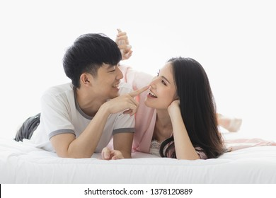A young happy Asian couple spending time and tease together on the bed, concept for love.