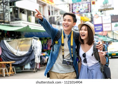 Young happy Asian couple tourist backpackers enjoy traveling in Khao San road during vacations in Bangkok, Thailand