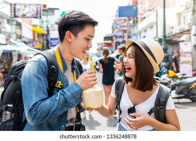 Young happy Asian couple tourist backpackers enjoy traveling in Khao San road during summer holidays in Bangkok, Thailand