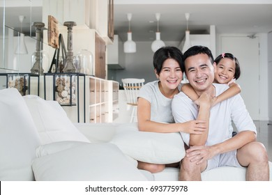 Young happy Asian family at home.