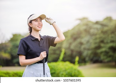 Young happy Asian female golfer feel satisfied after putting a golf ball in to hole