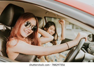 Young happy Asian girl best friends laughing and smiling in car during a road trip to vacation.