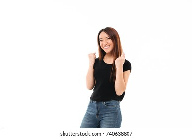 Young happy asian girl in casual wear showing winner gesture, looking at camera, isolated on white background