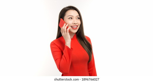 Young happy Asian girl smiling and talking on mobile phone while thinking isolated against white background