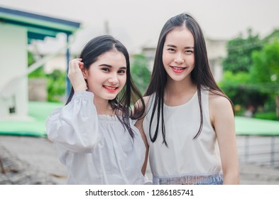 Young happy Asian girls best friends smile standing together and having fun looking at camera