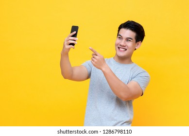 Young happy Asian man selfie with smartphone in colorful yellow background