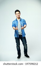 Young happy asian man showing thumbs up on gray background