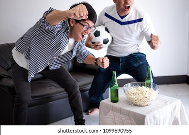 Young Happy Asian Men family or football fans watching soccer match on tv and cheering football team, celebrating with drink beer and eat popcorn at home, sports and entertainment concept.