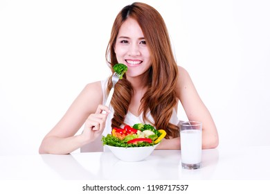 Young, happy asian woman eating healthy salad sitting on the table with green fresh ingredients and glass of milk on table on white background. Healthy lifestyle concept.