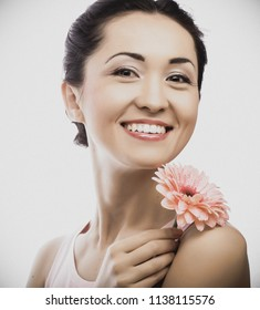 Young happy asian woman holding a pink gerbera, isolated on white