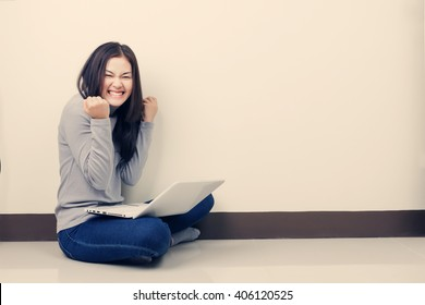 Young happy Asian woman with laptop sitting in the room. Winning in game.