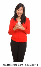 Young happy Asian woman smiling and using mobile phone