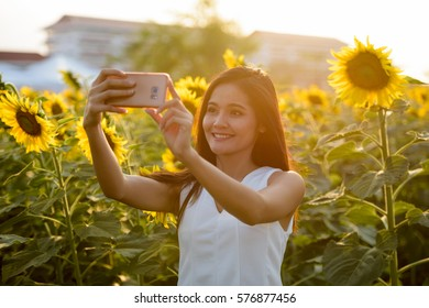 Young happy Asian woman smiling while taking selfie picture with mobile phone in the field of blooming sunflowers
