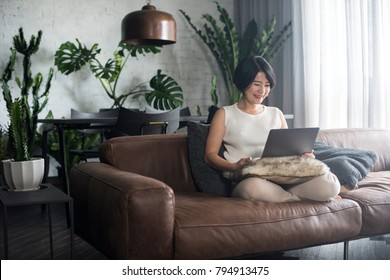 Young happy Asian woman using the computer at home.