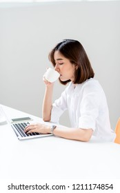Young happy Asian woman in a work office drinkg a cup of coffee
