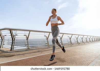 Young happy athletic woman in sport wear doing warming up training of run