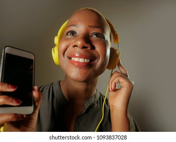 young happy and attractive afro American woman with yellow headphones and mobile phone listening to internet music song smiling cheerful isolated on grey green background in hipster lifestyle