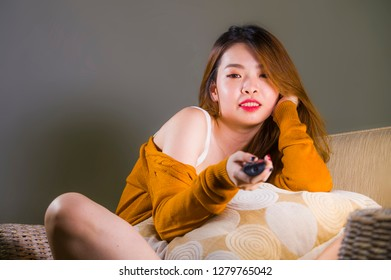 young happy and attractive Asian Chinese woman watching television at home sofa couch holding remote smiling relaxed enjoying comedy movie or TV show in domestic entertainment concept