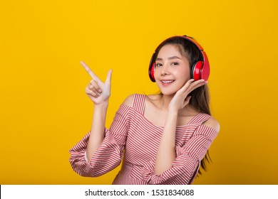 Young happy attractive Asian woman listening music using Bluetooth headphone, entertainment activity. Isolated on yellow background.