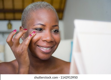 young happy and attractive black african American woman wrapped in towel applying makeup cosmetics using fingers putting base primer looking and smiling to the mirror in female beauty concept