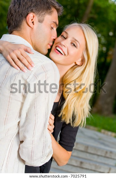 Young happy attractive embracing couple, outdoors