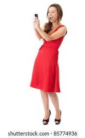Young happy attractive female in red dress takes photos using her mobile phone, shoot over white background