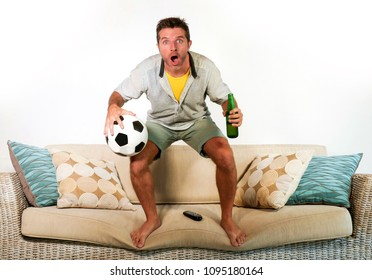 young happy attractive football fan man holding beer bottle and soccer ball watching game on television excited and nervous in disbelief shocked and surprised face expression