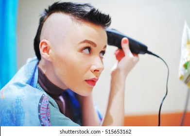 Young happy attractive girl shaves her hair on her head. skinhead punk model profile portrait.