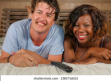 young happy and attractive mixed ethnicity couple with beautiful black African American woman and cheerful Caucasian man at home lying on bed watching tv show or comedy movie laughing together
