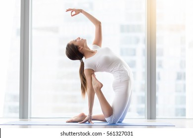 Young happy attractive woman practicing yoga, sitting in Camel exercise, Ustrasana pose, mudra, working out, wearing sportswear, white t-shirt, pants, indoor full length, floor window with city view