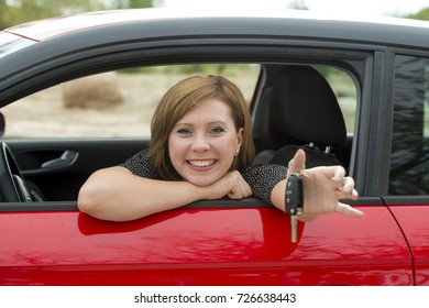 young happy attractive woman smiling proud sitting at driver seat holding and showing car key in new automobile buying and renting concept and insurance and rental advertising