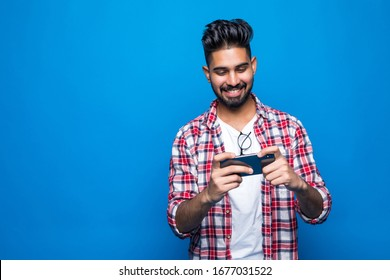 Young happy bearded indian man play games on mobile phone posing over blue wall background