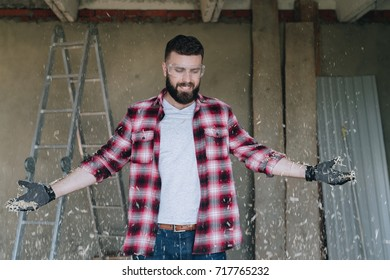 Young happy bearded man hipster carpenter in construction glasses stands in workshop. From above fly sawdust. Woodwork.Carpentry, construction, repair.Guy,dressed in plaid shirt, throws wood shavings.