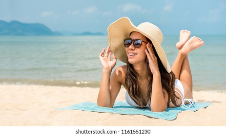 Young happy beautiful Asian woman with sunhat lying on stomach taking a sunbath relaxing at the beach on summer vacations