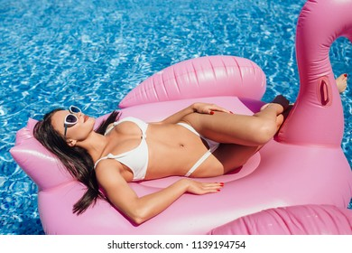 Young happy beautiful brunette girl with a beautiful figure sunbathing on the inflatable flamingo in the pool.