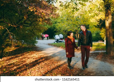 Young happy beautiful couple in love smiling woman and man in casual warm clothes walking by hands on road in autumn city park outdoors in sunny day. Love relationship family people lifestyle concept