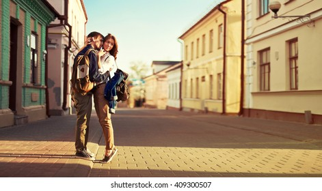 Young happy beautiful couple in love kissing on the street panorama in summer have fun together hipster style
