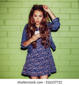 young happy beautiful long-haired brunette lady in blue dress with jeans jacket near the green brick wall with a surprised expression on her face looking to smartphone phone and correct her sunglasses