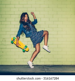 young happy beautiful long-haired brunette girl in blue dress having fun with yellow plastic penny board skateboard in front of the green brick wall