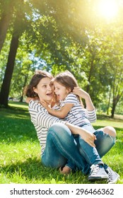 Young Happy Beautiful Mother and Daughter have Fun in Sunny Day on Meadow