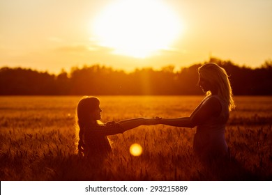 Young happy beautiful mother and her daughter . Happy family jumping together in a circle having fun and expressing emotions of joy, freedom, success. Silhouettes on sunny sky