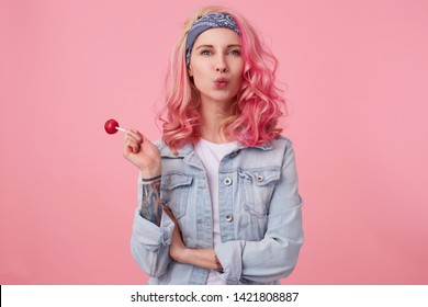 Young happy beautiful pink haired lady in denim shir, holding a lollipop, looks at the camera, sedns kiss, stands over pink background.